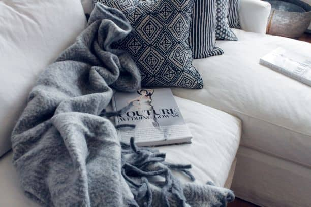 Blanket and pillows on couch with magazine