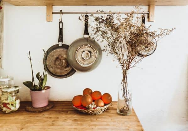 Pans hanging on wall, flowers in vase on table