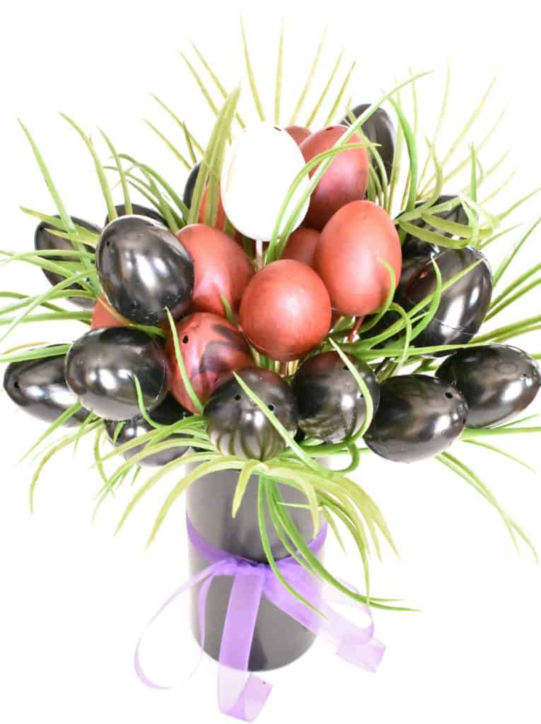 Black, red, and white egg bouquet with palm fronds
