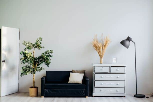 Super small couch  and dresser with normal-sized lamp and potted plant