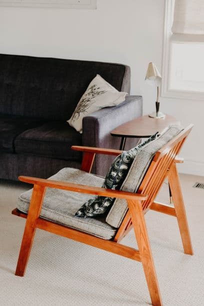 low profile couch and wooden chair with small lamp on side table