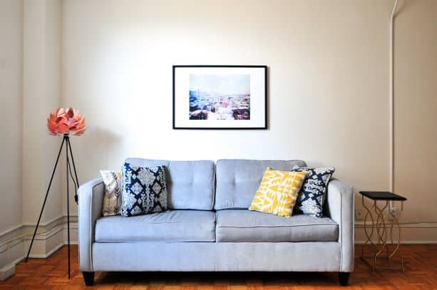 Asymmetry in living space, couch with pillows, upright lamp