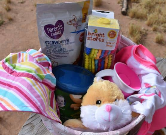 Easter basket filled with stuffed bunny, baby treats, beach gear, sippy cup, and linking rings