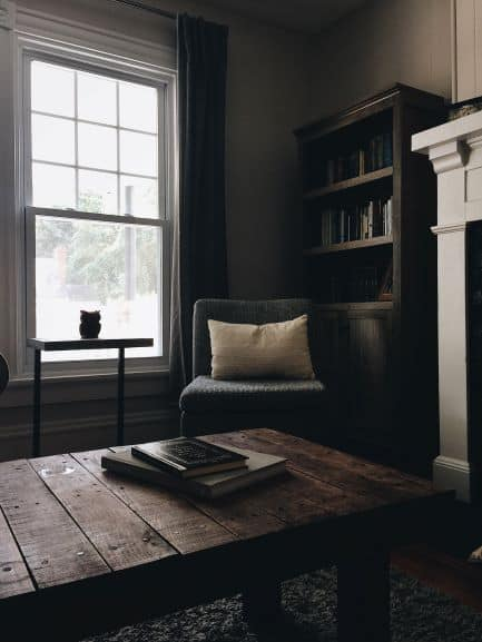 Rustic coffee table in foreground, chair with pillow beside window, in front of rustic bookcase beside fireplace, overall unified style and feeling