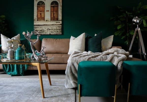 Dark green walls, tan sofa, light photo above sofa