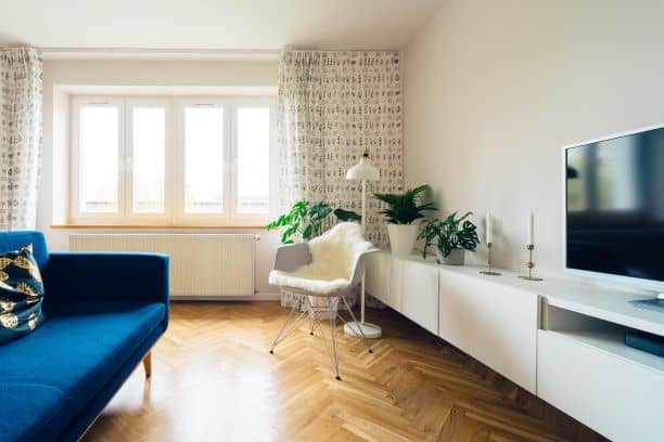 Blue sofa, white chair, TV, white TV cabinets create unity with variety