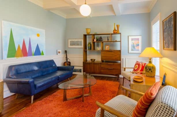Blue couch, two tan chairs, orange rug
