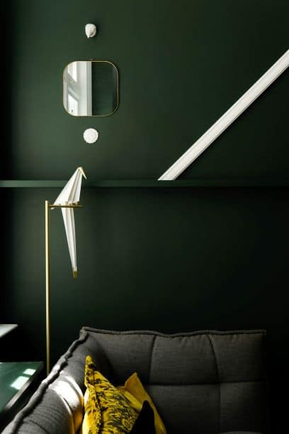 molding line draws the eye around the space and creates movement, dark green walls, mirrors, origami bird, couch