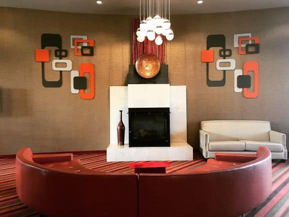 Asymmetrical balance of couch on one side of fire place and vase on fireplace base creates movement in living room with red couch, white fireplace, light fixture