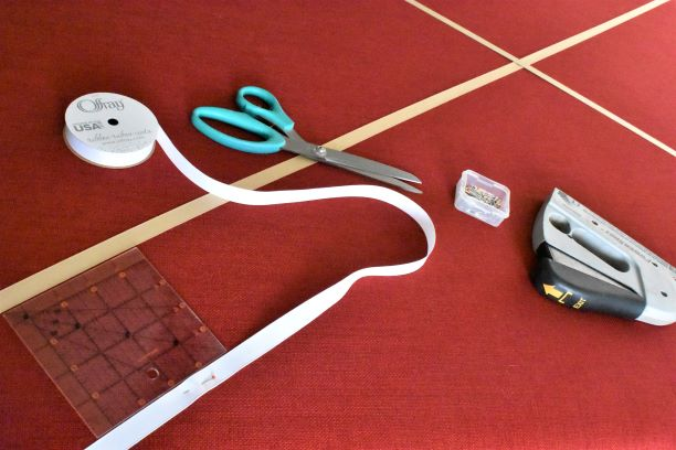 scissors, ribbon, staples, pins, sewing guide on top of picture board