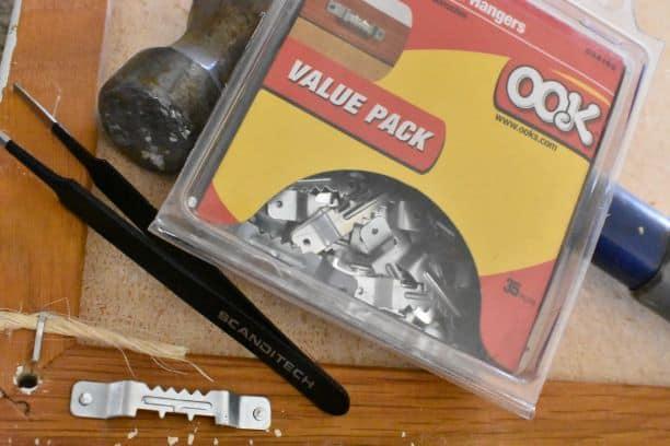 picture hangers, tweezers, and hammer