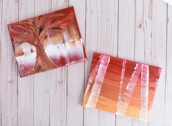 photo of two tree paintings, one lone tree and one forest of birch trees, both in gold, copper, red, and white tones